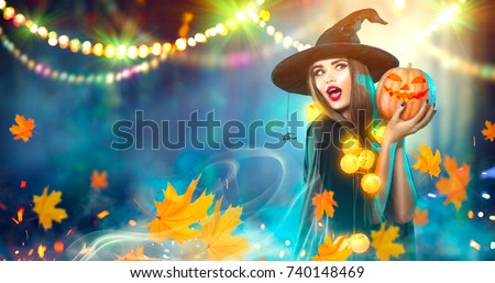 Halloween Witch with a carved Pumpkin and magic lights in a dark forest. Beautiful young surprised woman in witches hat and costume holding pumpkin. Wide Halloween party art design #740148469