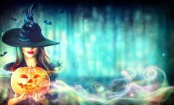 Halloween Witch with a magic Pumpkin in a dark forest. Beautiful young woman in witches hat and costume holding carved pumpkin. Wide Halloween art design