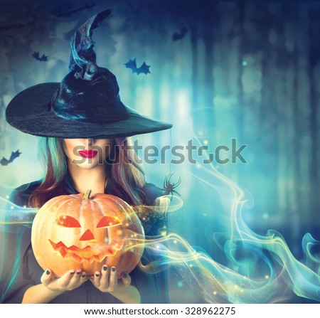 Stock Photo Halloween Witch with a magic Pumpkin in a dark forest. Beautiful young woman in witches hat and costume holding carved pumpkin. Halloween art design