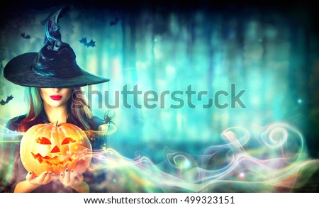 Stock Photo Halloween Witch with a magic Pumpkin in a dark forest. Beautiful young woman in witches hat and costume holding carved pumpkin. Wide Halloween art design