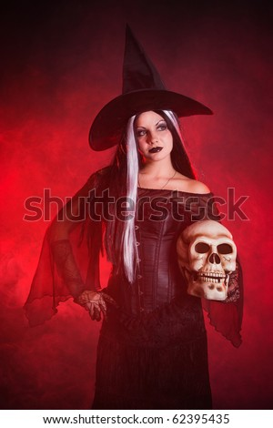 Halloween witch with a skull over color background with smoke
