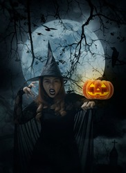 Halloween witch with pumpkin monster head standing over cross, church, crow, birds, dead tree, full moon and cloudy spooky sky, Halloween mystery concept