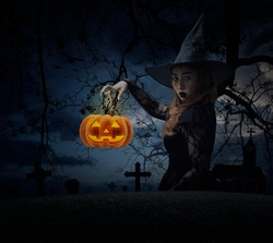 Halloween witch with pumpkin monster head standing over grass, dead tree, cross, birds with church over spooky cloudy sky, Halloween mystery concept