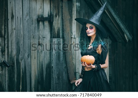 Halloween Witch with pumpkin. Pretty young woman in witch costume. Halloween decor. Toned image. Copy space.