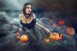 Halloween Witch with Pumpkins and magic lights in a dark room. Beautiful young sexy woman in witches costume sitting with pumpkins and candles. Witchcraft scene art design Halloween party art design.