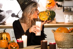 Halloween Witch with pumpkins. Beautiful young woman in a witch costume by candlelight at the table. Halloween decor.