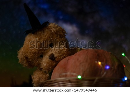 Halloween with pumpkins and a teddy bear. The garland glows in different colors, a festive mood. #1499349446