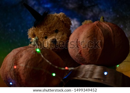 Halloween with pumpkins and a teddy bear. The garland glows in different colors, a festive mood. #1499349452