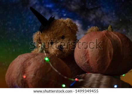 Halloween with pumpkins and a teddy bear. The garland glows in different colors, a festive mood.