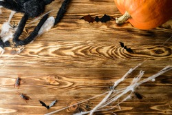 Halloween wooden background with spider web, spiders and ghosts as symbols of Halloween on the wooden background, cobweb, pumpkin and copy space for text