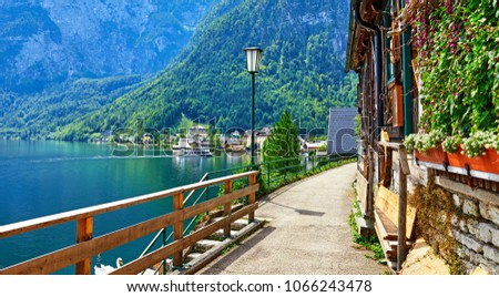Hallstatt Austria vintage architecture and old houses in picturesque austrian mountains Alps on lake Hallstattersee. Old street along the lake banks with wooden fence and lantern.