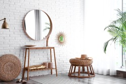 Hallway interior with big round mirror, table and decor near brick wall