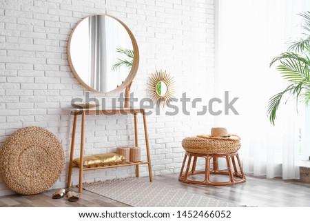 Hallway interior with big round mirror, table and decor near brick wall