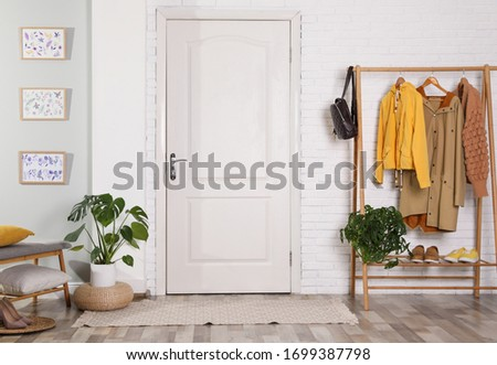 Hallway interior with stylish furniture, clothes and plants Сток-фото ©
