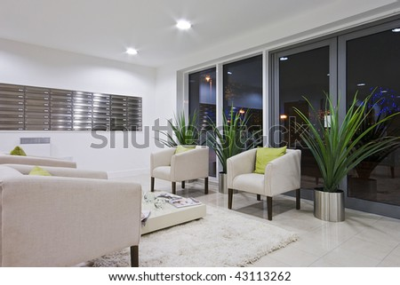 hallway of a modern development with post room and sofas #43113262