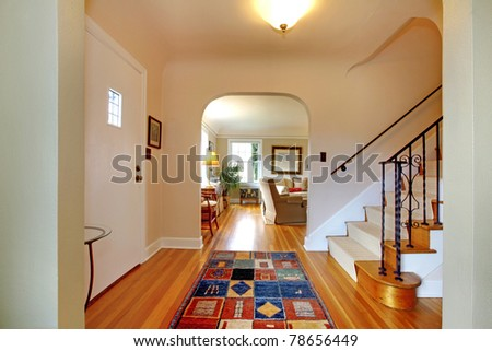 Hallway with large staircase and dining room