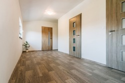 Hallway with various contemporary room door designs, wooden floor and one window. All doors have a wooden texture, glass panels of various shapes and fittings made of matt stainless steel.