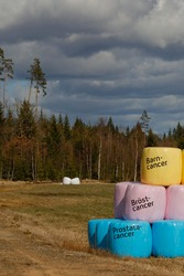 Halmstad, Sweden Colored hay bales, with signs in Swedish saying: yellow: child cancer, pink: breast cancer, blue: prostate cancer.