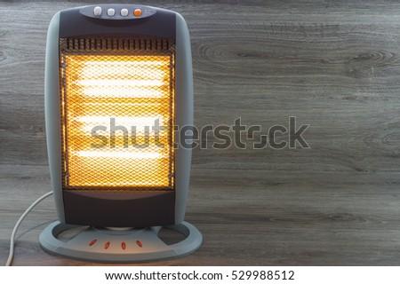 Halogen Electric Stove illuminated and radiating on gray background