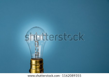 Halogen light bulb in holder set against a blue background with glow to illustrate EU decision to ban them #1162089355