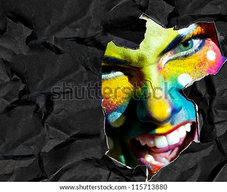 Haloween women color face art mad portrait black crumpled torn paper background white teeth evil smiling copy space