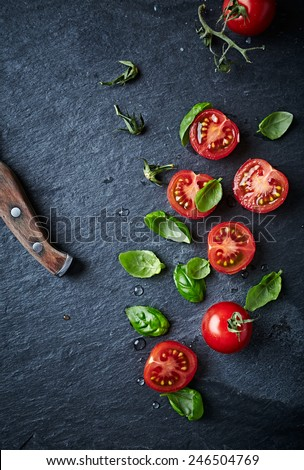 Halved cherry tomatoes and basil leaves on black slate