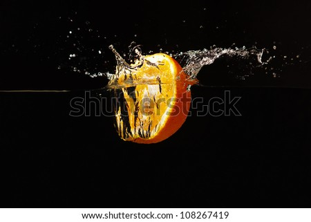 Halved fresh orange falling into the water with a splash on a black background closeup