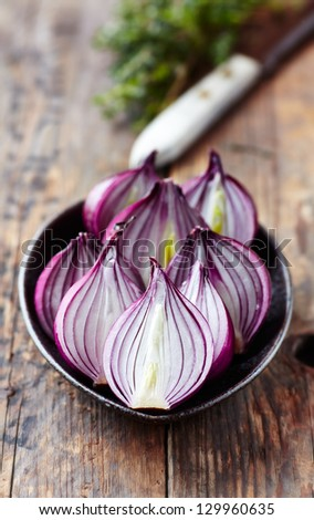 Halved red onions on a ceramic plate