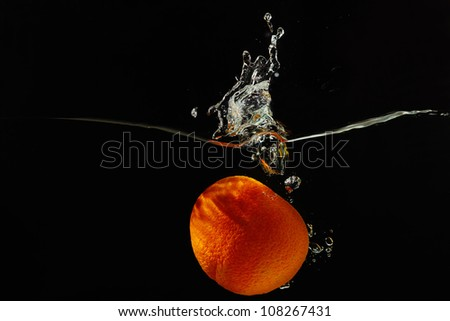 Halved ripe orange falling into the water with a splash on a black background closeup
