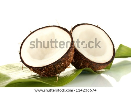 halves of coconut with green leaf on white background close-up