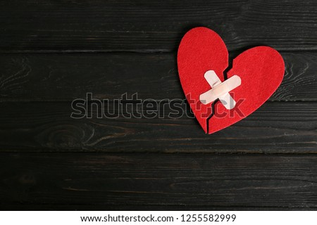Halves of cut felt heart joined with adhesive plasters on dark wooden background, top view. Space for text #1255582999