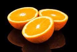 Halves of fruits orange mandarin isolated on black background, mirror reflection
