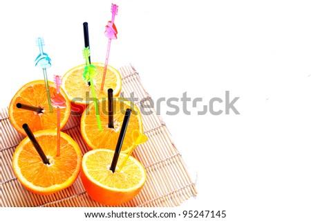 Halves of oranges with straws