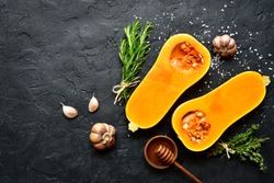 Halves of raw organic butternut squash with spices and ingredients for making on a black slate, stone or concrete background.Top view with copy space.