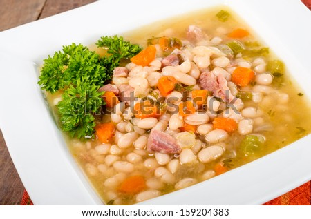 Ham and bean soup garnished with parsley in a white bowl