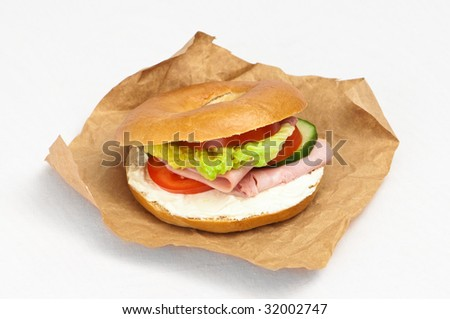 Ham and cheese bagel with salad in brown paper wrapping