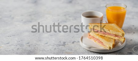 Ham and cheese sandwich, coffee with milk and orange juice on table in coffee shop. Typical breakfast in many countries. Large image for banner. Foto stock ©