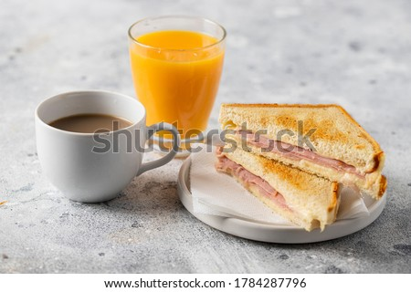 Ham and cheese sandwich, cup of coffee with milk and orange juice glass on concrete table in coffee shop at the morning. Typical breakfast in many countries.  Foto stock ©