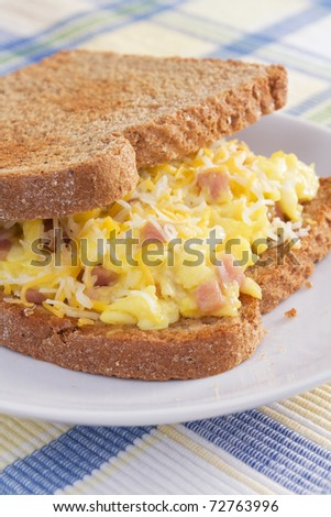 Ham, eggs, and cheese sandwiched between two slices of toasted wheat bread.