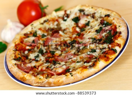ham, mushroom and vegetable pizza and tomato at the back