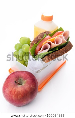Ham sandwich, apple, green grapes and orange juice in a lunch box isolated on white