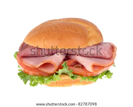 Ham sandwich with lettuce and tomato on a bun isolated on white
