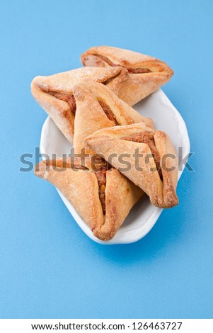 Hamantaschen cookies for Jewish festival of Purim on blue background