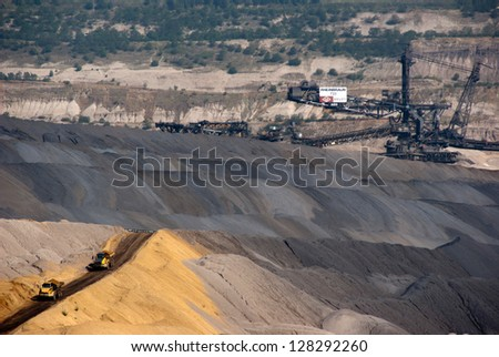 HAMBACH, GERMANY - SEPTEMBER 1: Very large trucks and one of the world's largest bucket-wheel excavators digging coal in one of the world's deepest open-pit mines in Hambach on September 1, 2010