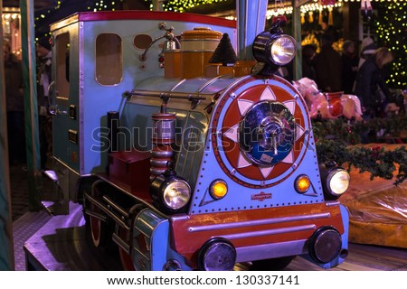 HAMBURG - DECEMBER 1: Old locomotive on a merry-go-round in a winter evening at the Christmas market around the town hall in Hamburg, Germany on December 1, 2012.