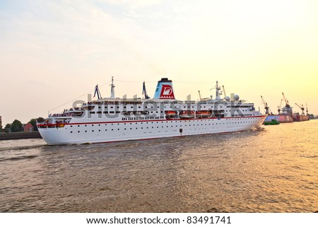 HAMBURG, GERMANY - 25 AUGUST: the famous cruise liner Deutschland with the film crew of the TV series Loveboat leaves the harbor in sunset for an overseas trip at August 25, 2011 in Hamburg, Germany.