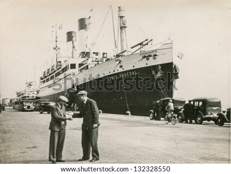 HAMBURG, GERMANY, CIRCA 1932 -  unidentified man discuss on harbor with Monte Pascoal ocean liner circa 1932 in Hamburg. Delivered in 1931 served for 1372 third class and 1028 tween decks passengers.