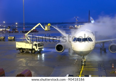 HAMBURG, GERMANY - DECEMBER 6: Deicing of the Lufthansa plane before take off on December 6, 2011 in Hamburg, Germany. The deicing applied by major european airport due to cold and snowy conditions.