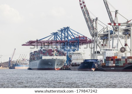 Hamburg, Germany - july 5: Giant ship in container harbor with tall cranes in Hamburg Harbor, Germany on july 5, 2013