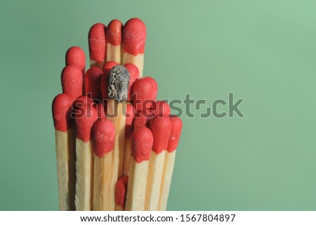 Hamburg /Germany - November 03, 2019: Close-up of a single burnt match in a group of unused matches - burnout, exhaustion, stress and work-life-balance concept
